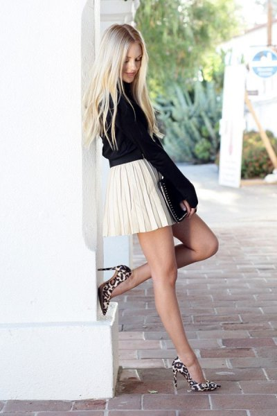 black knitted sweater with stand-up collar and white pleated skirt