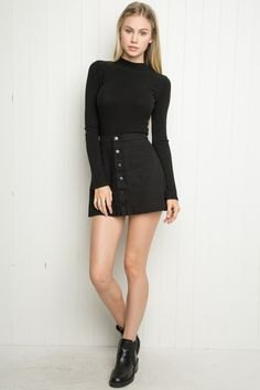 black long-sleeved sweater with stand-up collar and mini cord skirt