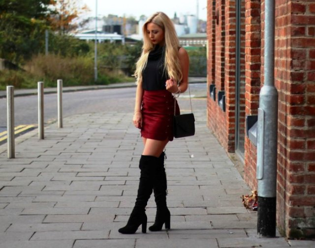 black sleeveless top with stand-up collar, burgundy mini skirt and high boots