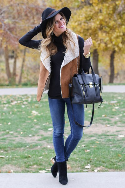 black mock-neck sweater with camel lambskin vest and blue jeans