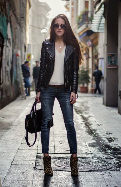black moto jacket with white chiffon blouse with V-neck and boots with leopard print