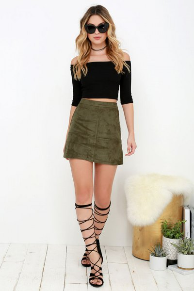 Black strapless crop top with an olive green mini skirt and gladiator shoes