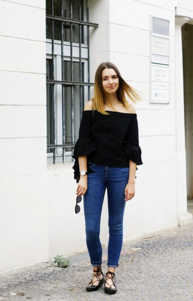 black off-the-shoulder blouse with half sleeves and blue skinny jeans