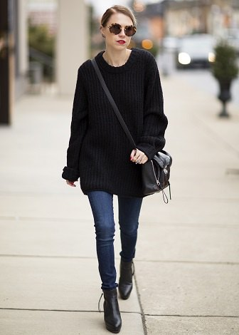 black oversized sweater with blue skinny jeans and leather ankle boots