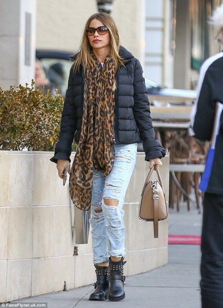 black padded jacket with a silk scarf with a leopard print and ripped light blue jeans