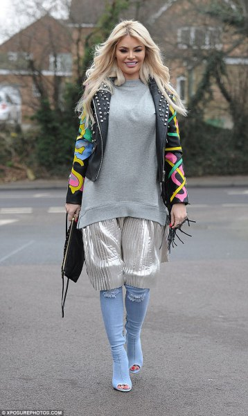 black printed leather jacket with rivets, silver shorts and knee-high boots made of light blue denim with open toes