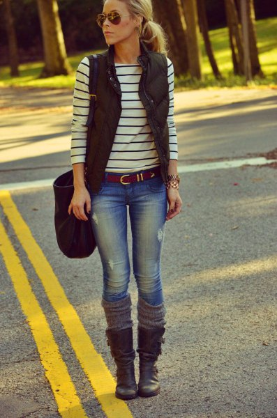 black puffer vest with a striped long-sleeved T-shirt and boots in the middle of the calf