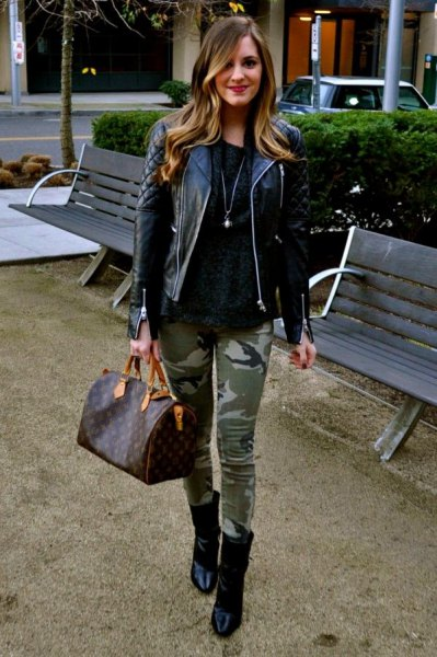 black quilted leather jacket with sweater with scoop neckline and camouflage gaiters