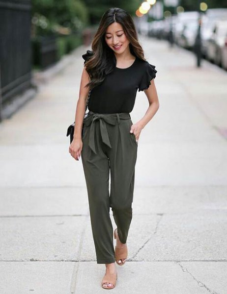 black t-shirt with ruffle sleeves and army green slim fit trousers on the front