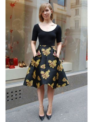 black, figure-hugging top with a scoop neckline and half sleeves and a knee-length skater skirt with a floral pattern