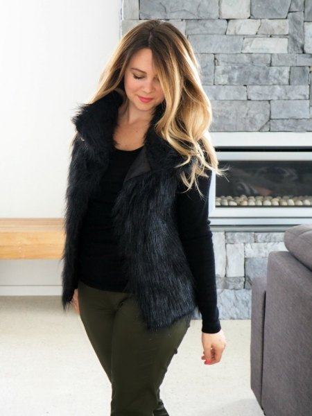 Black long-sleeved t-shirt with a scoop neckline, fur vest and gray slim fit jeans