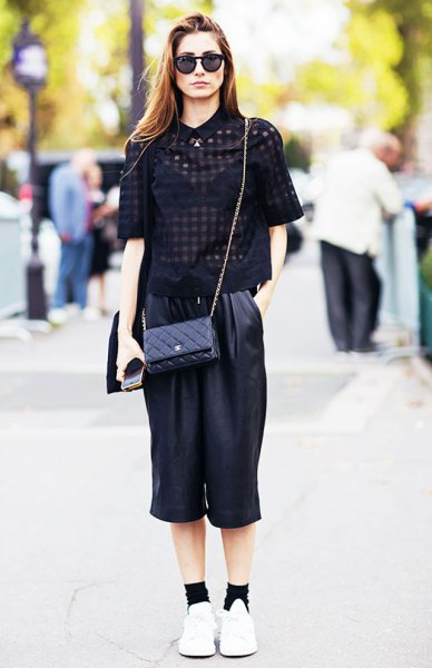 black, semi-transparent short-sleeved blouse with cropped trousers with wide legs made of leather