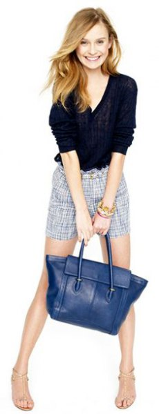 black shirt with gray checkered, flowing shorts and dark blue leather handbag