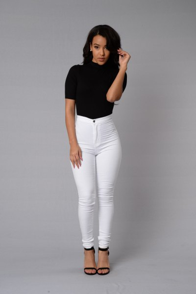 black short-sleeved mock-neck top with white skinny jeans with a high waist
