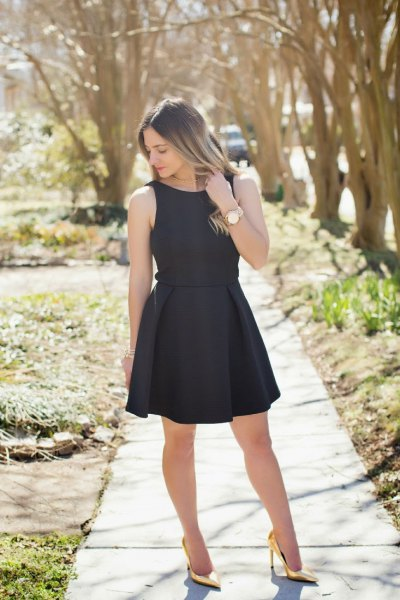 black sleeveless, figure-hugging mini dress with gold high heels