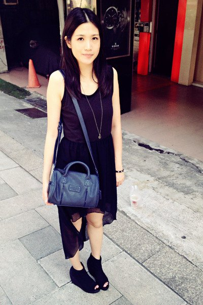 black sleeveless dress with high chiffon and scoop neckline and dark blue handbag