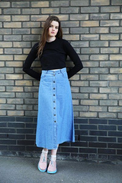 black, slightly shortened top with bell sleeves and blue skirt with a long denim button on the front