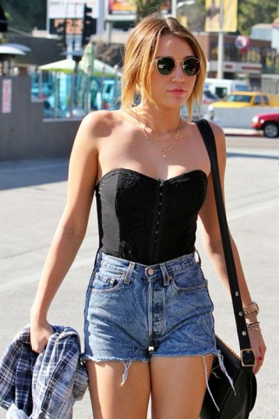 black strapless sweetheart top with high-waisted blue mini jean shorts