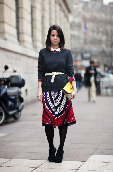 black sweater and red and white printed skirt