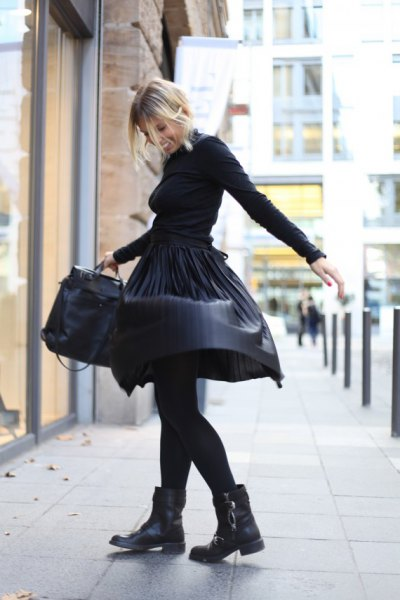 black sweater with matching leather pleated skirt and motorcycle boots