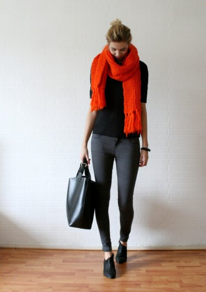 black sweater with an orange fringed scarf and gray skinny jeans