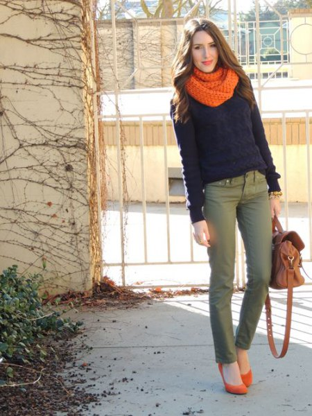 black sweater with an orange knitted scarf and gray chinos