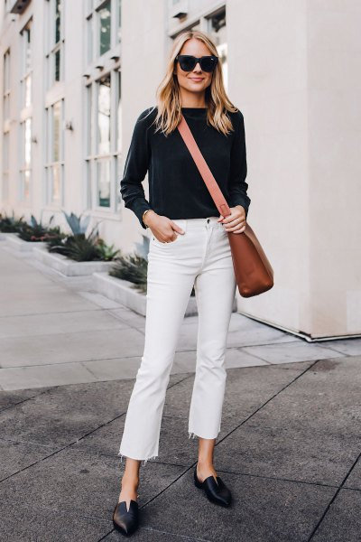 black sweater with white, cropped jeans and a brown leather shoulder bag