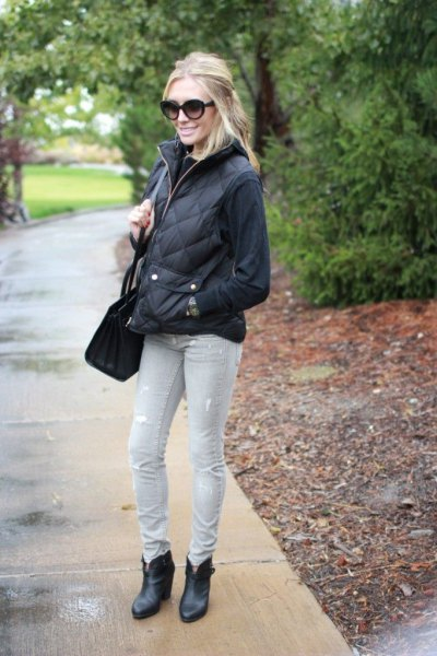 black sweatshirt with quilted puffer jacket and light gray jeans