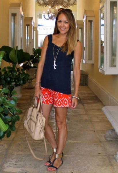 Relaxed tank top with a black sweetheart neckline and orange shorts with a tribal print