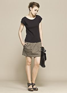 black t-shirt with green mini skirt and flat sandals
