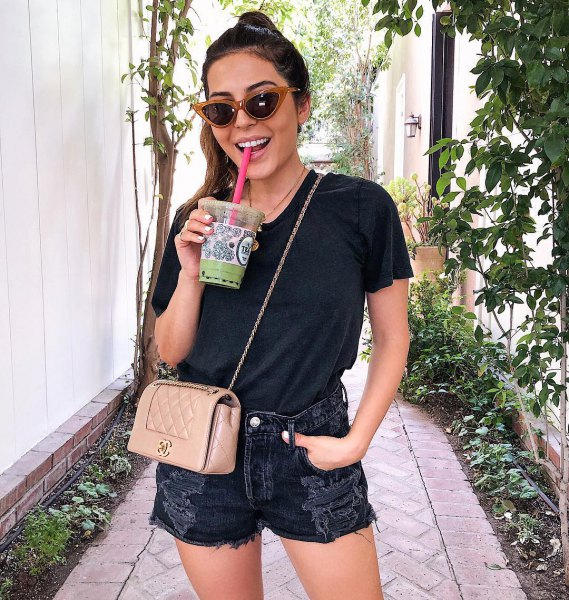black t-shirt with ripped denim shorts and pink wallet