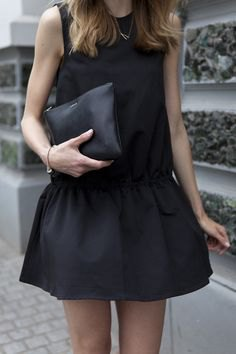 black tank top with minirater skirt and leather handbag