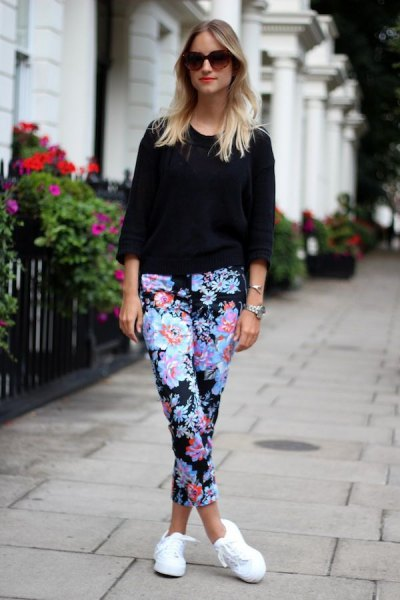 black three-quarter sleeve sweater with blue-cut trousers with a floral pattern and white sneakers