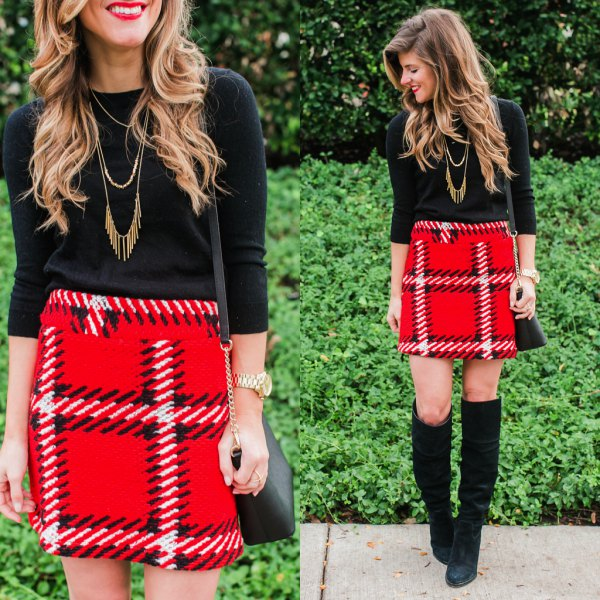 black sweater with three-quarter sleeves and red mini skirt made of checked wool with a high waist