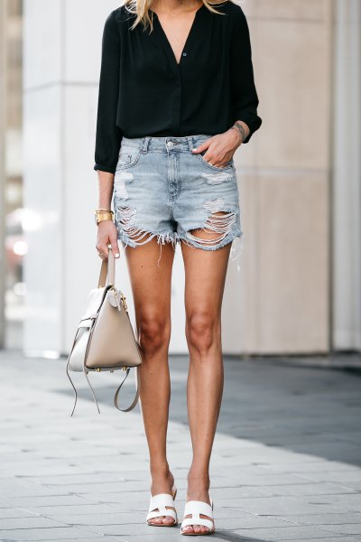 black blouse with V-neck and heavily ripped mini-denim shorts