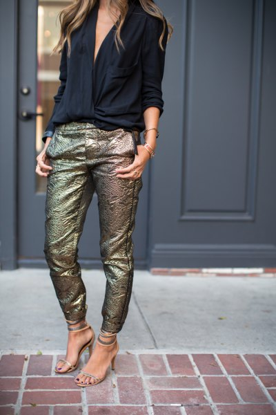 black blouse with V-neckline and slim-fitting trousers made of sequined gold