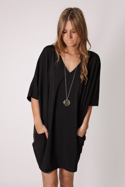black tunic dress with V-neckline and long necklace