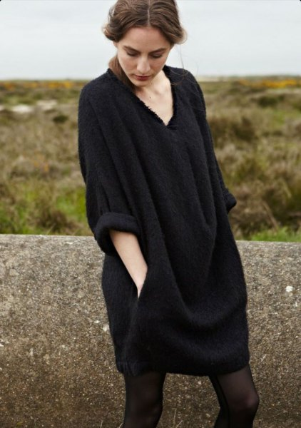 black sweater dress with wide sleeves and V-neckline and stockings