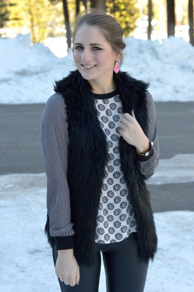 black vest with tribal-printed long-sleeved top and dark gray jeans