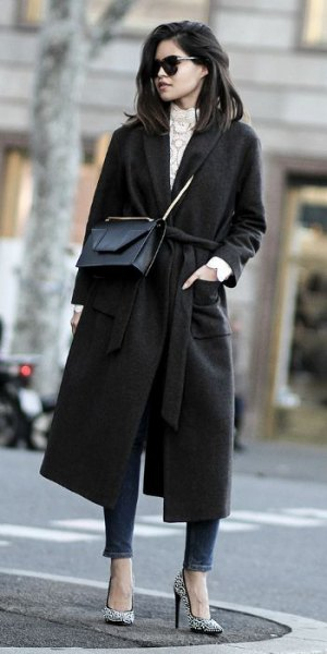 black walker coat with gray knitted sweater with stand-up collar and ankle jeans