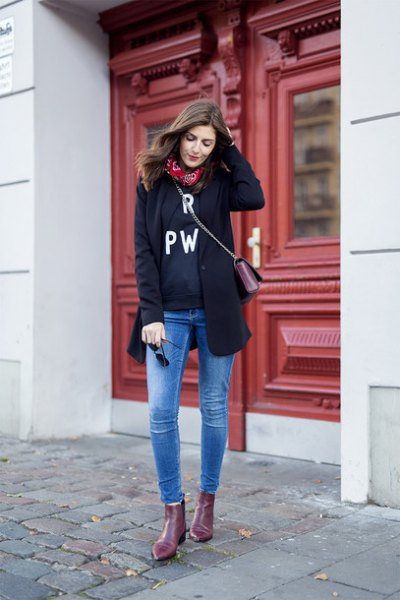 black wool coat with graphic sweatshirt and blue skinny jeans