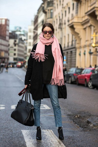 black wool coat with a light pink fringed scarf and black, narrow-cut jeans