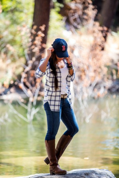 blue and white checked hiking jacket with gray knee-high leather boots