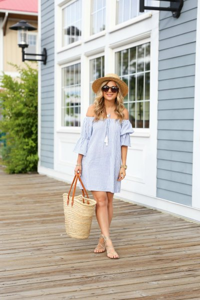 Blue and white striped strapless mini dress with a straw shopping bag