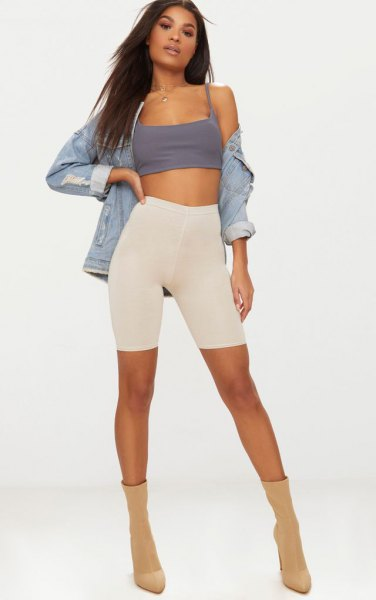 blue denim jacket with a gray, short tank top and ivory-colored cycling shorts