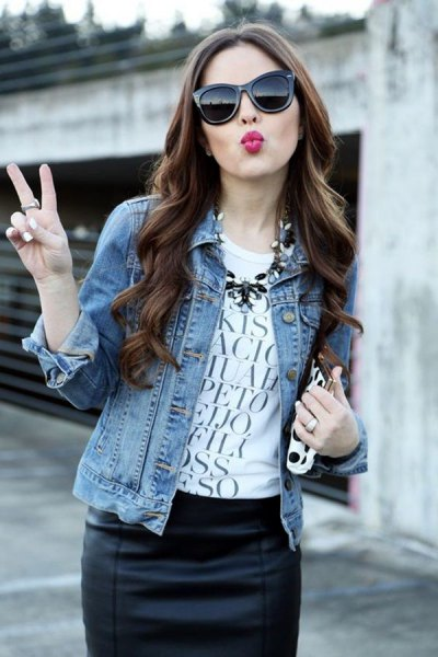 blue denim jacket with white graphic t-shirt and black leather skirt