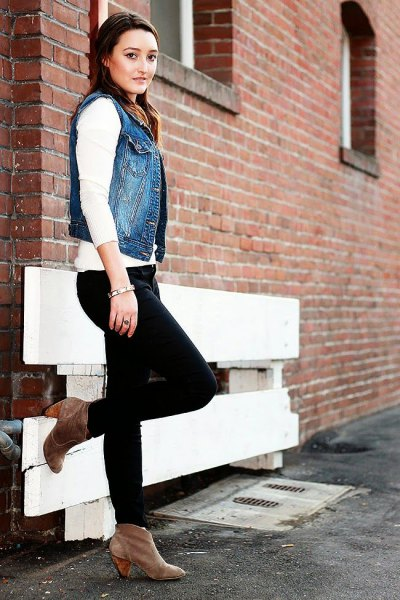 blue denim motorcycle vest with white sweater and black jeans