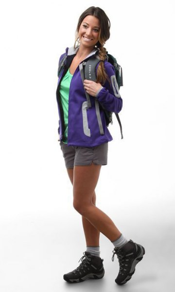 blue hiking jacket with gray mini-shorts and black trail shoes