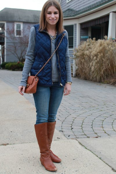 blue quilted vest with gray long-sleeved top and brown knee-high boots