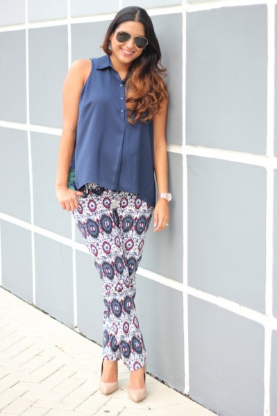blue sleeveless blouse with button closure, white trousers with tribal print
